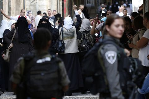 Palestinians shout slogans in front of Israeli security forces who block a street leading to the Al-Aqsa mosque compound, in the Muslim quarter in Jerusalem's Old City yesterday.