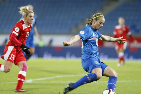 Harpa Þorsteinsdóttir taking the ball to the opposition.