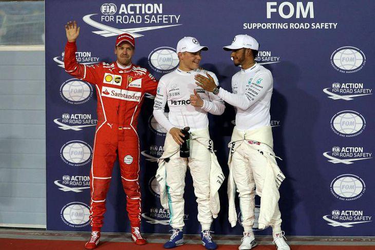 Lewis Hamilton (l.t.h) og Sebastian Vettel samgleðjast Valtteri Bottas (í miðjunni) með ráspól hans í ...