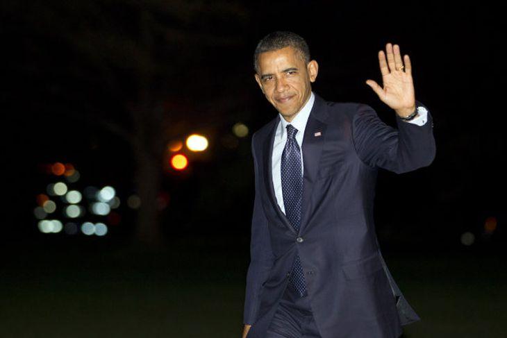 Barack Obama veifar til blaðamanna.