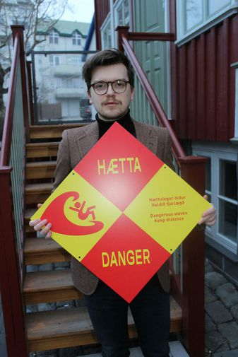 Ívar Björnsson with a warning sign he designed.