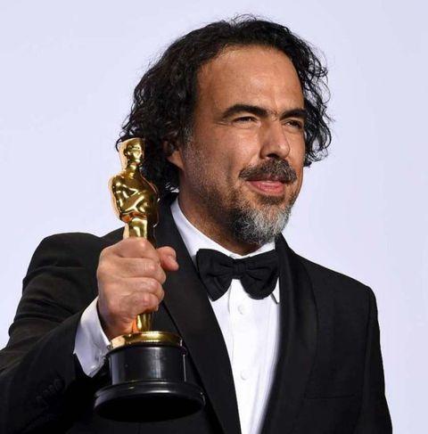 Alejandro G. Iñárritu kreppir hnefann um styttuna.