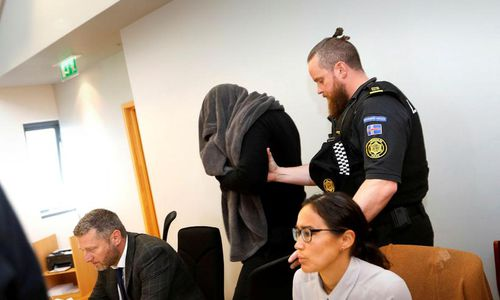 Thomas Møller Olsen covering his face from photographers at the Reykjanes district court today.