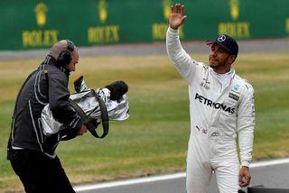 Lewis Hamilton veifar löndum sínum í stúkum Sivlerstone að tímatöku lokinni.