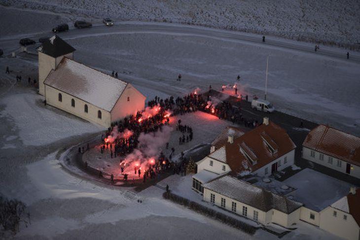 Tendrað var á rauðum neyðarblysum eftir að kórinn hafði sungið.
