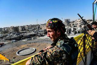 Hermenn SDF virða fyrir sér skemmdirnar við Al-Naim torgið í Raqqa.