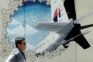 Malasískur maður gengur framhjá veggmynd af MH370-vélinni.