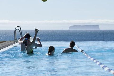 The beautiful views from the pool at Hofsós, North Iceland with Drangey island rising from the ocean in the distance.