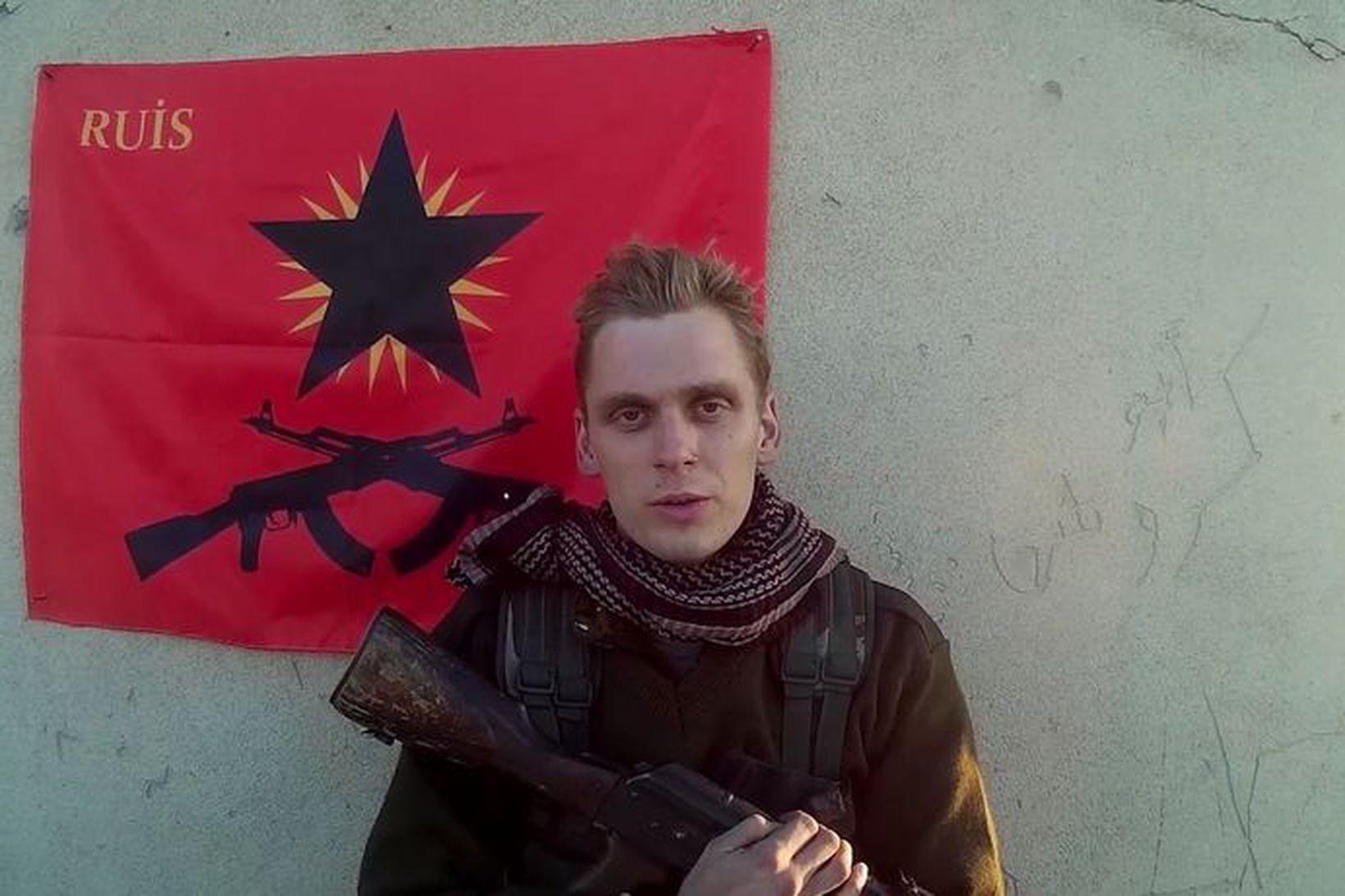 Skjáskot úr myndbandi gríska anarkistahópsins RUIS. Haukur stendur við fána …