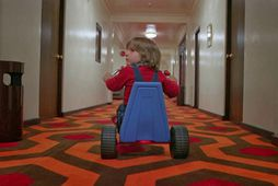 Danny, leikinn af Danny Lloyd, hjólar um ganga Overlook-hótelsins í The Shining.