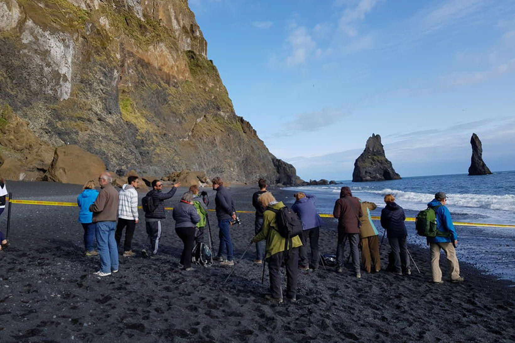Lögregluborðinn vekur athygli ferðamanna í Reynisfjöru sem kanna aðstæður.