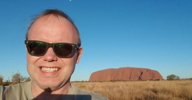 Ferðalangurinn með klettinn Uluru í bakgrunni.