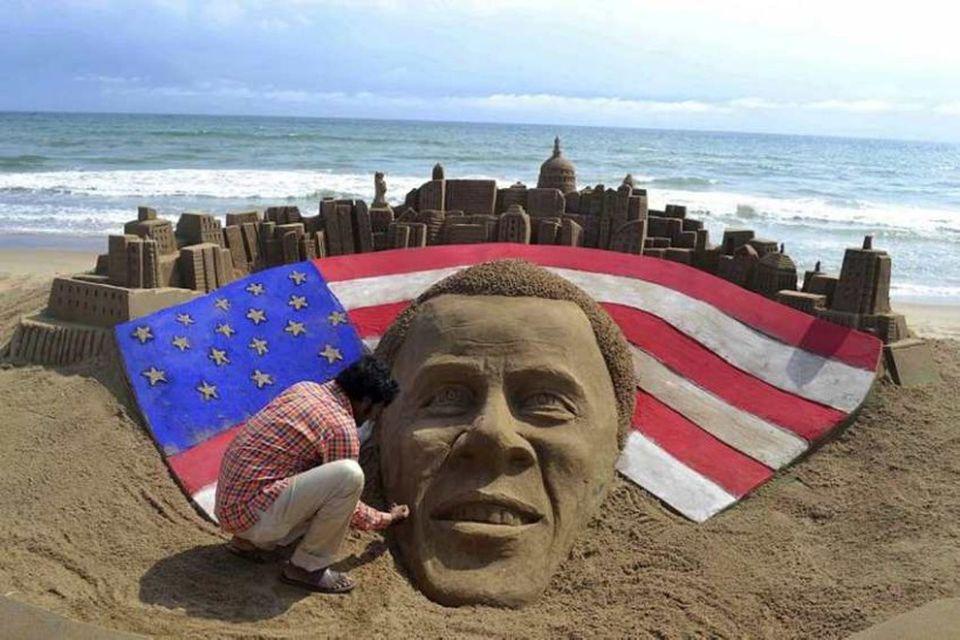 Indverski listamaðurinn Sudaran Pattnaik leggur lokahönd á risavaxið verk úr sandi af andliti Baracks Obama, …