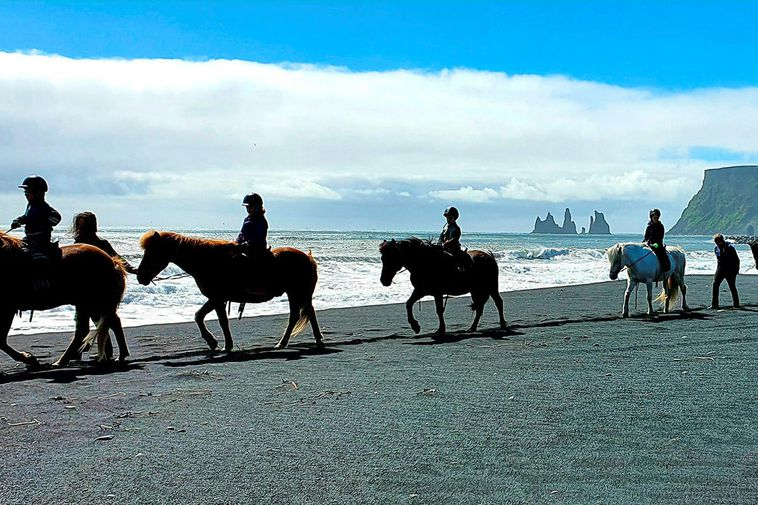 Young riders on the beach. Reynisdrangar sea stacks in the background.