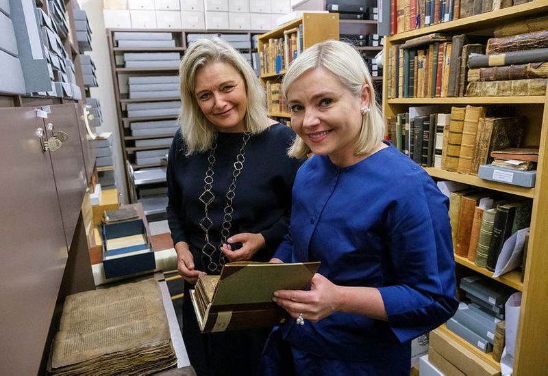 Education Minister Lilja Alfreðsdóttir, right, looks at an old manuscript at the Árni Magnússon Institute for Icelandic Studies, guided by the institute's director, Guðrún Nordal.