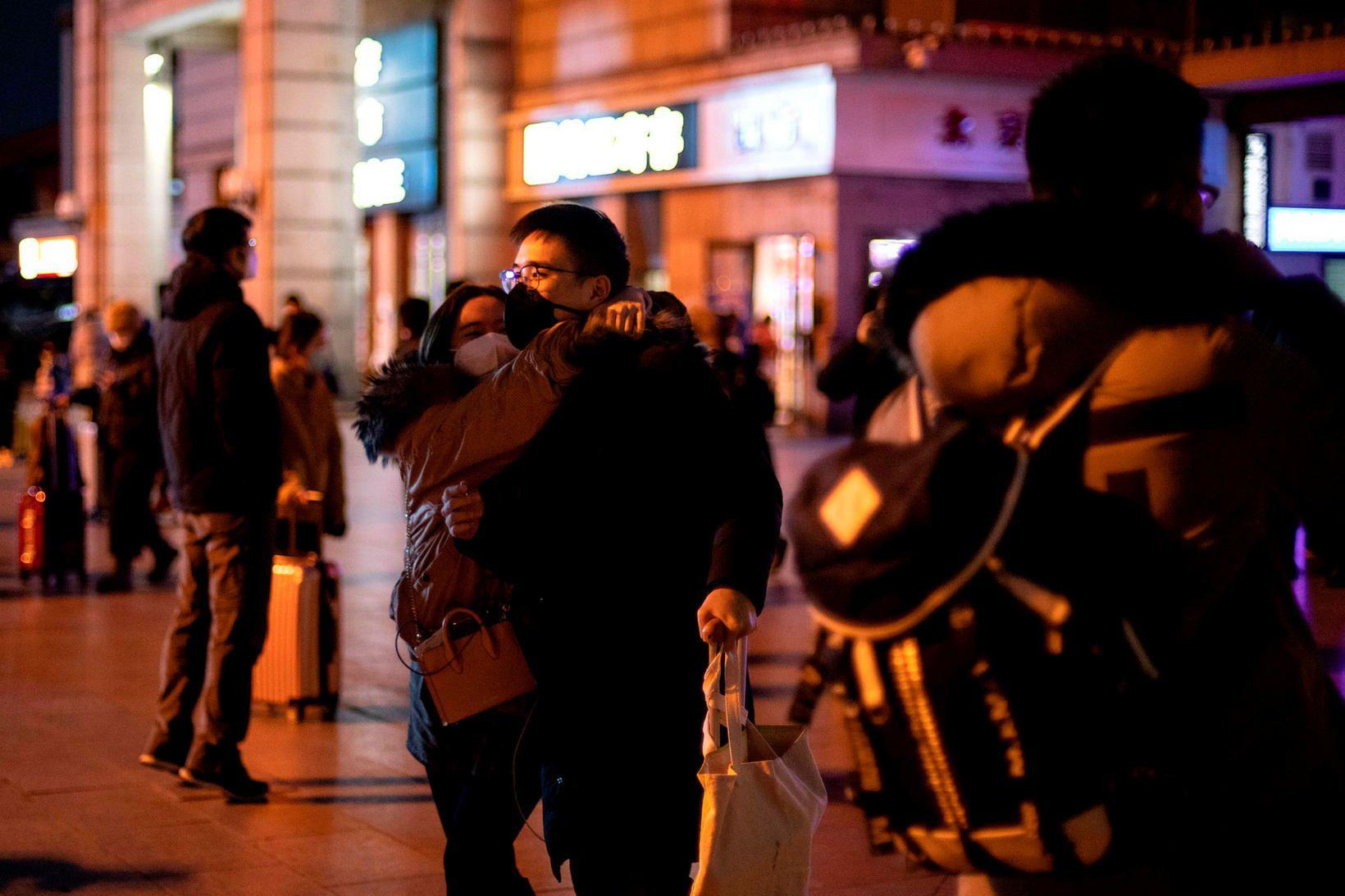 Grímuklæddir farþegar á aðallestarstöðinni í Peking.