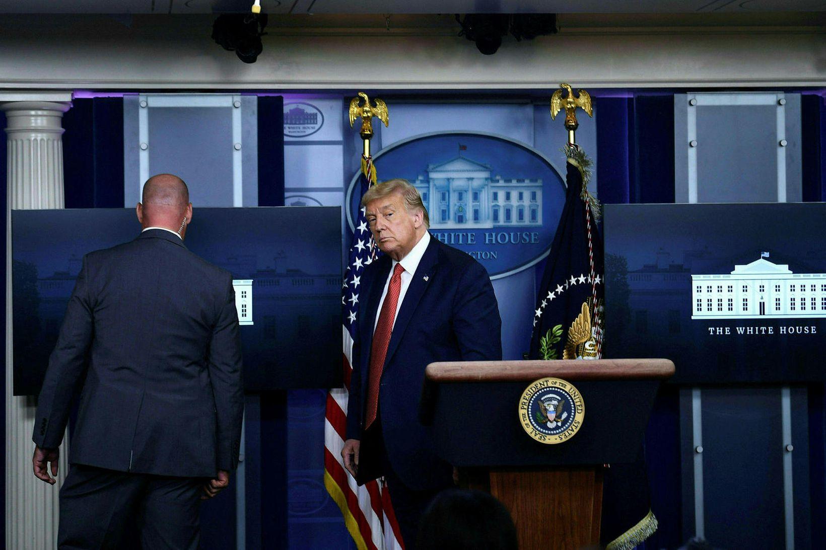 Starfsmaður leyniþjónustunnar fylgir Donald Trump Bandaríkjaforseta úr púlti. Blaðamannafundinum var …