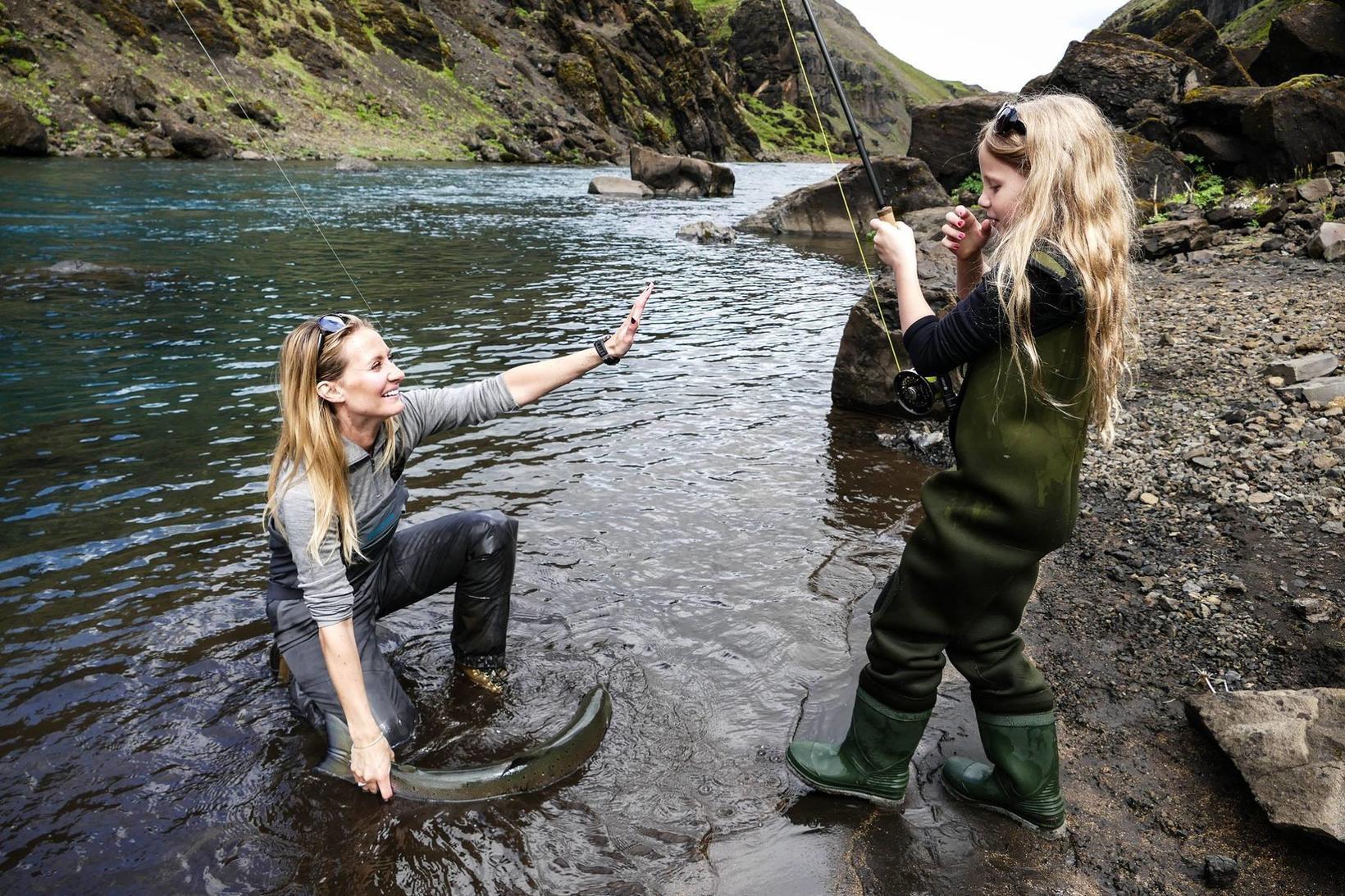 Valgerður Árnadóttir sporðtekur lax í Stóru-Laxá sem Matthildur dóttir hennar …