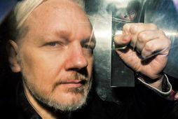 Julian Assange steytir hnefann um borð í fangaflutningabíl í London 1. maí síðastliðinn.