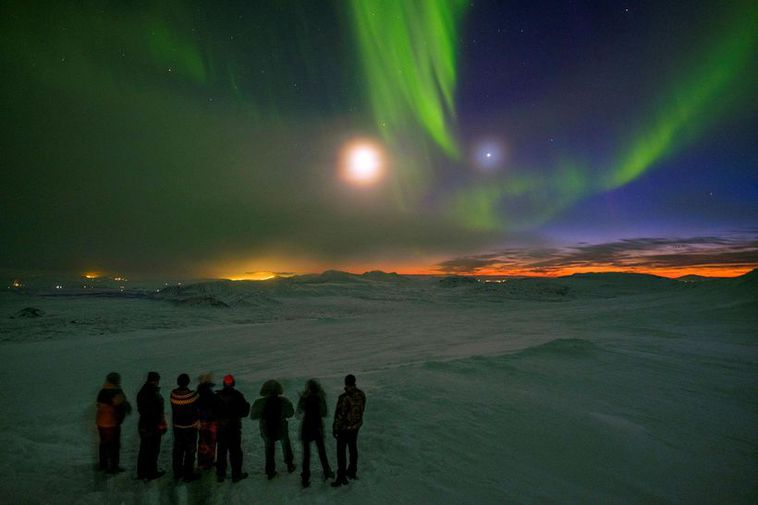 Tourists observing Northern Lights in Iceland.