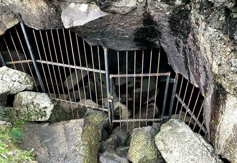 The cave has been closed off with a locked fence and gate.