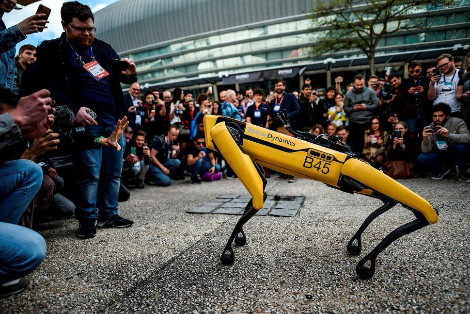 Gestir á tæknisýningu í Lissabon skoða vinnuróbota frá Boston Dynamics. ...