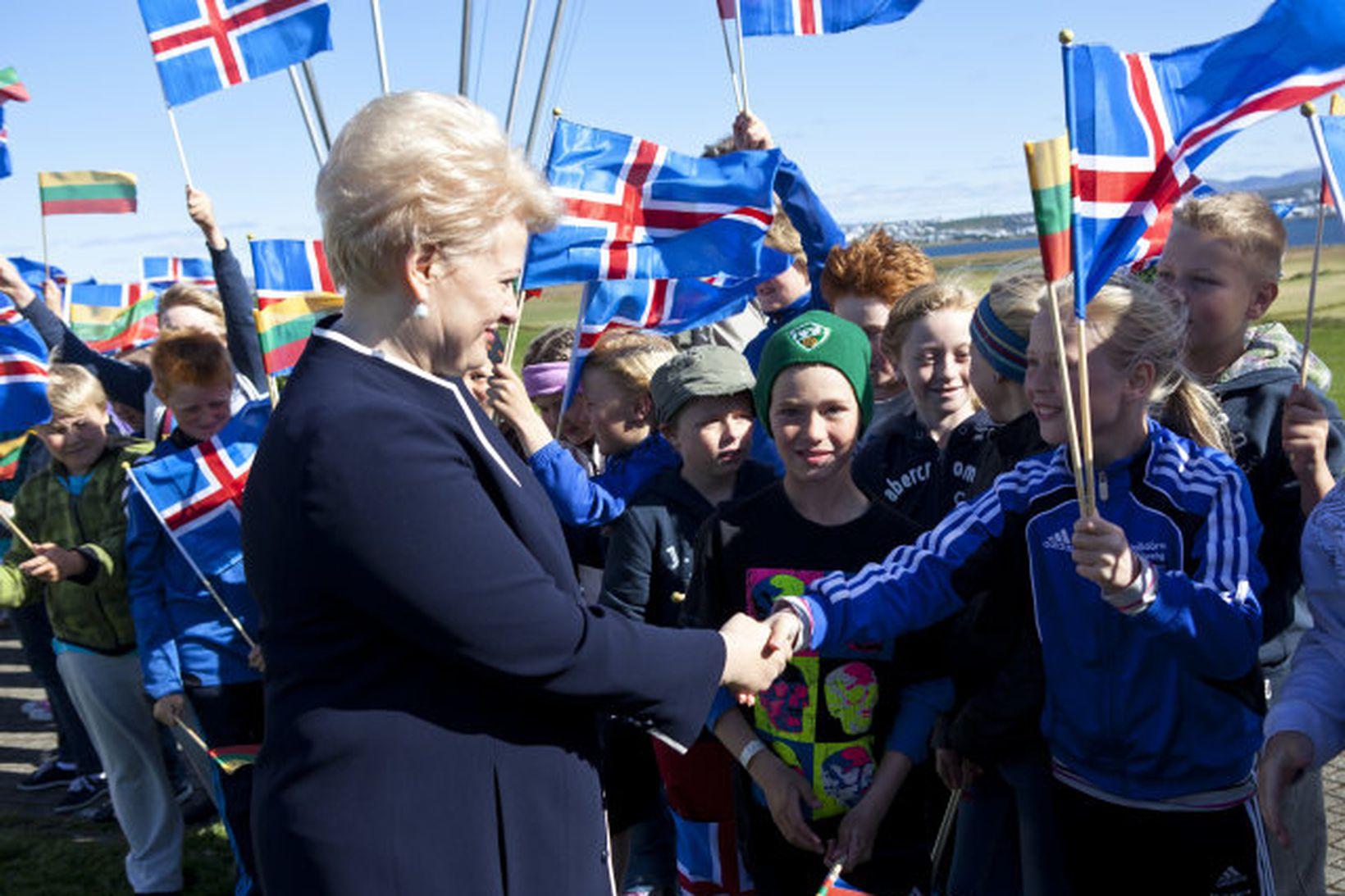 Dalia Grybauskaitė, forseti Litháens, heilsar börnum í heimsókn sinni til …