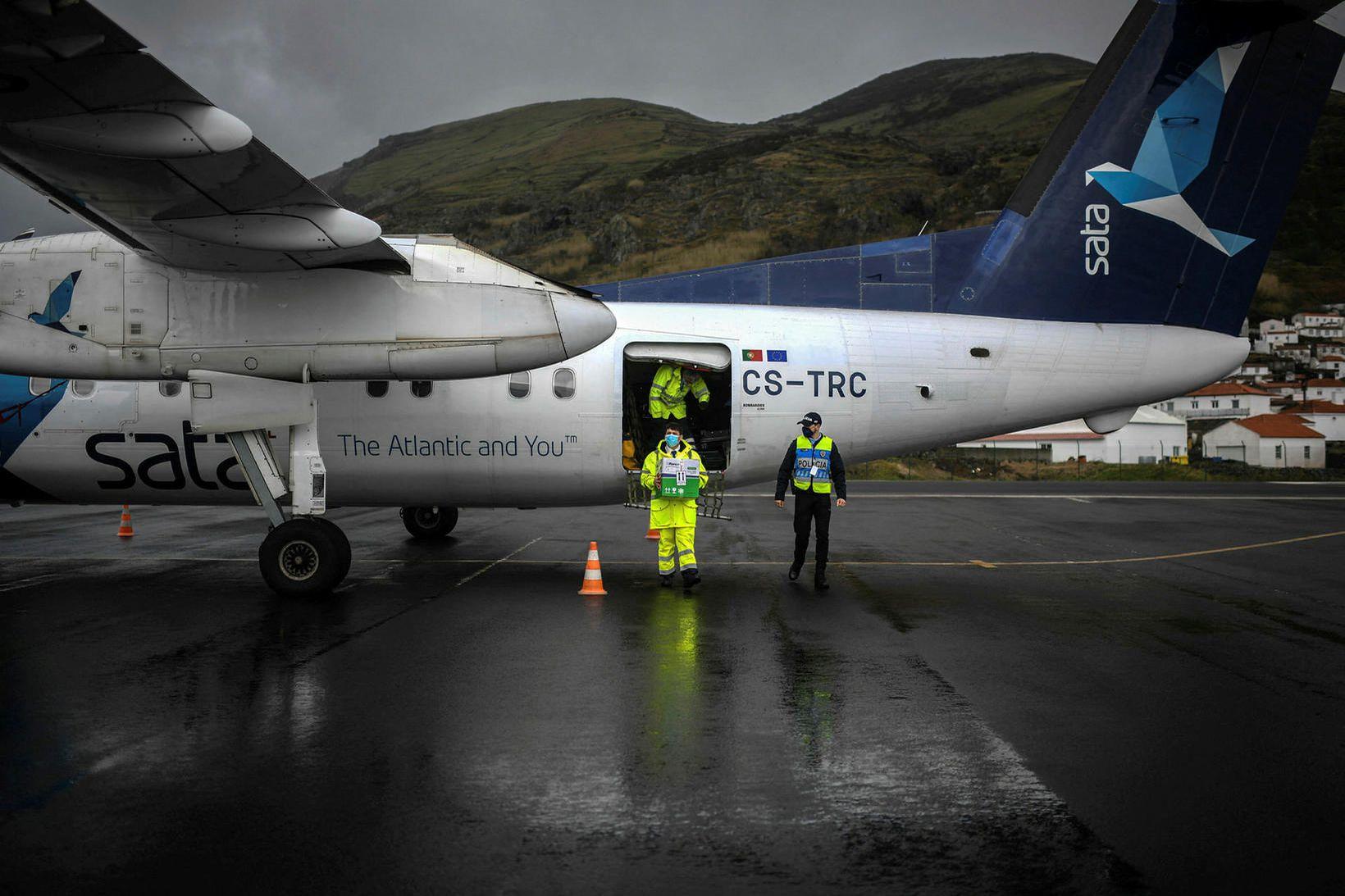 Starfsmaður tekur Covid-19 bóluefni úr flugvél á Asoreyjum.