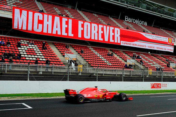 Sebastian Vettel í Barcelona í dag. Í stúkunni er minnst Michael Schumacher, sigursælasta ökumann Ferrari.