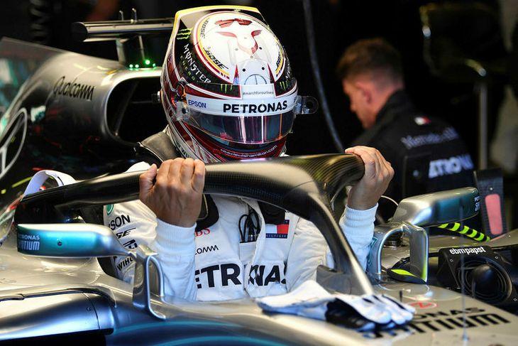 Lewis Hamilton smeygir sér niður í stjórnklefa Mercedesbílsins rétt fyrir upphaf kappakstursins í Melbourne.