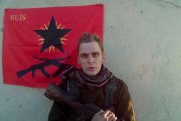 Skjáskot úr myndbandi gríska anarkistahópsins RUIS. Haukur stendur við fána hópsins.