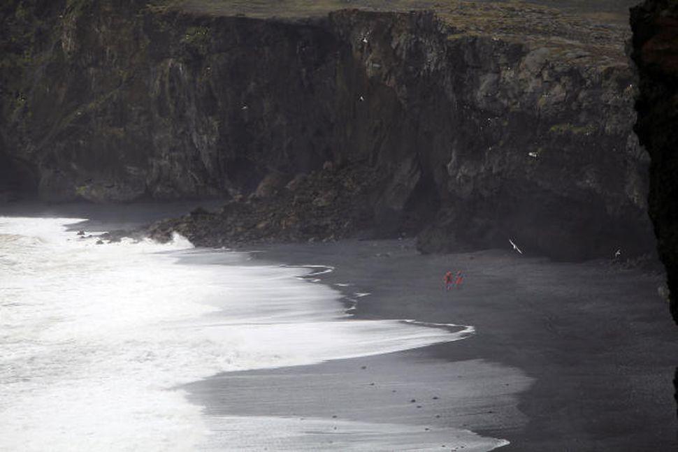 Björgunarsveitarmennirnir eru smáir undir hömrunum við Kirkjufjöru þar sem fólkið ...