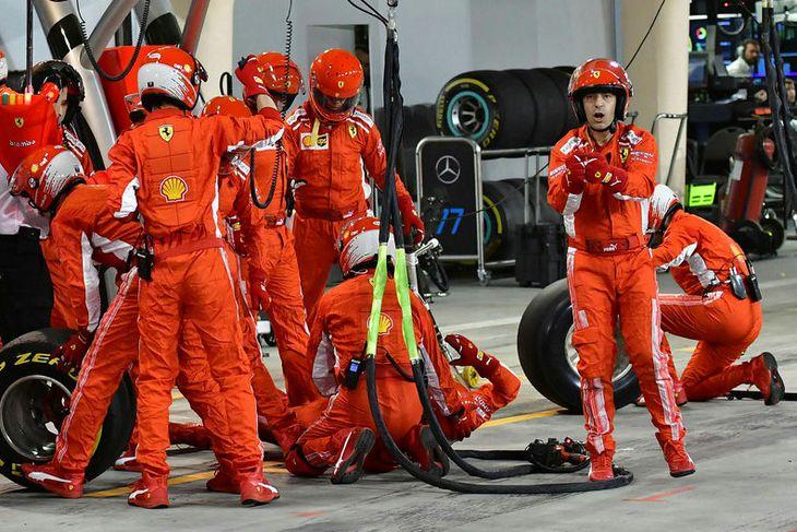 Dekkjamanni Ferrari veitt fyrsta hjálp við bílskúr liðsins eftir hin misheppnuðu dekkjaskipti.