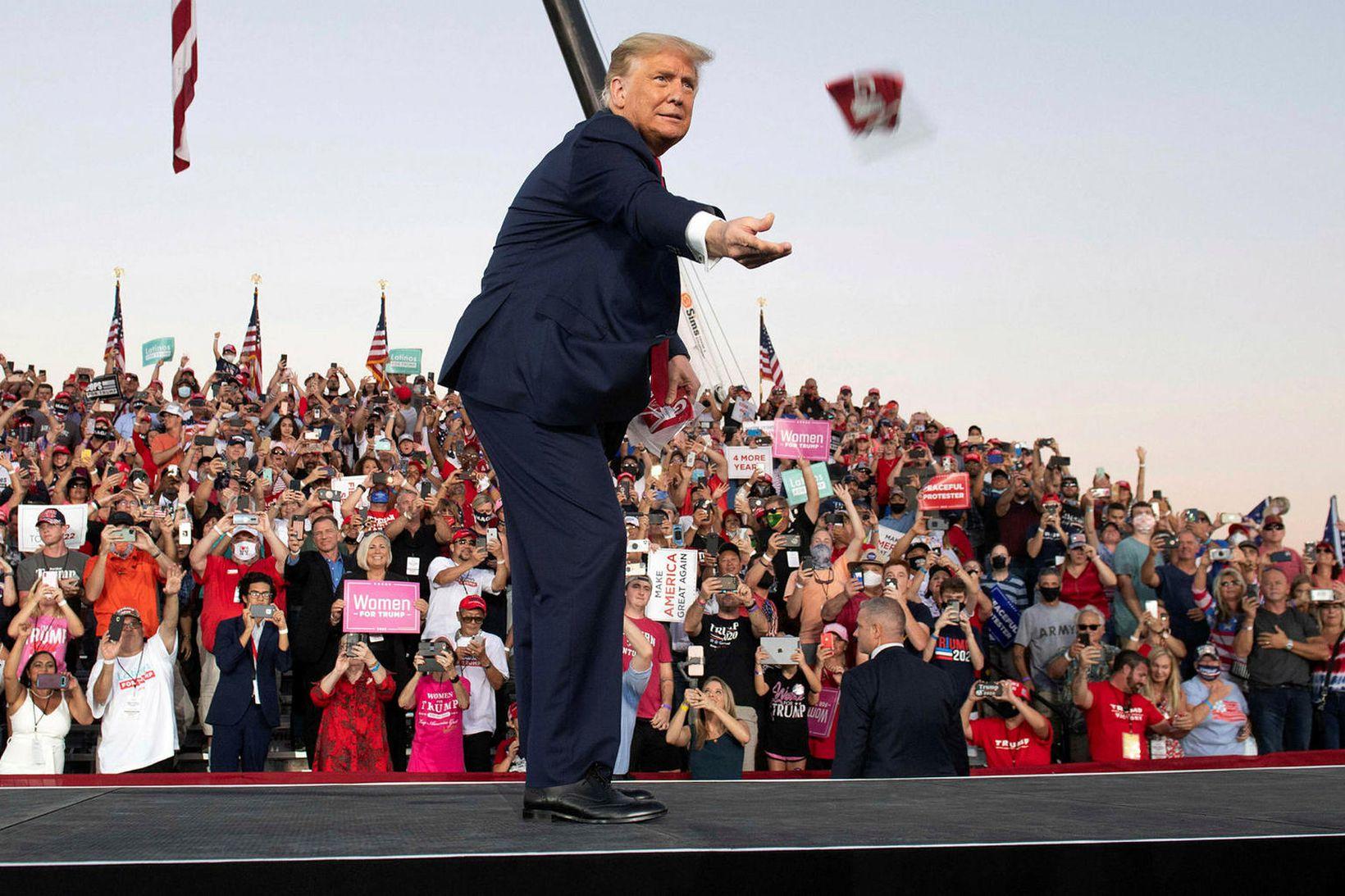 Donald Trump sést hér henda grímum í áhorfendur.