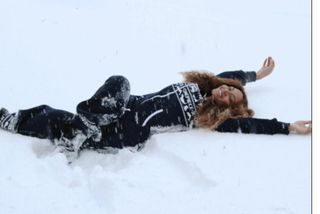 Beyoncé velti sér um í snjónum í bláum heilgalla.