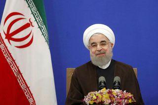 Rouhani brosir er hann heldur ræðu í Tehran á laugardag.
