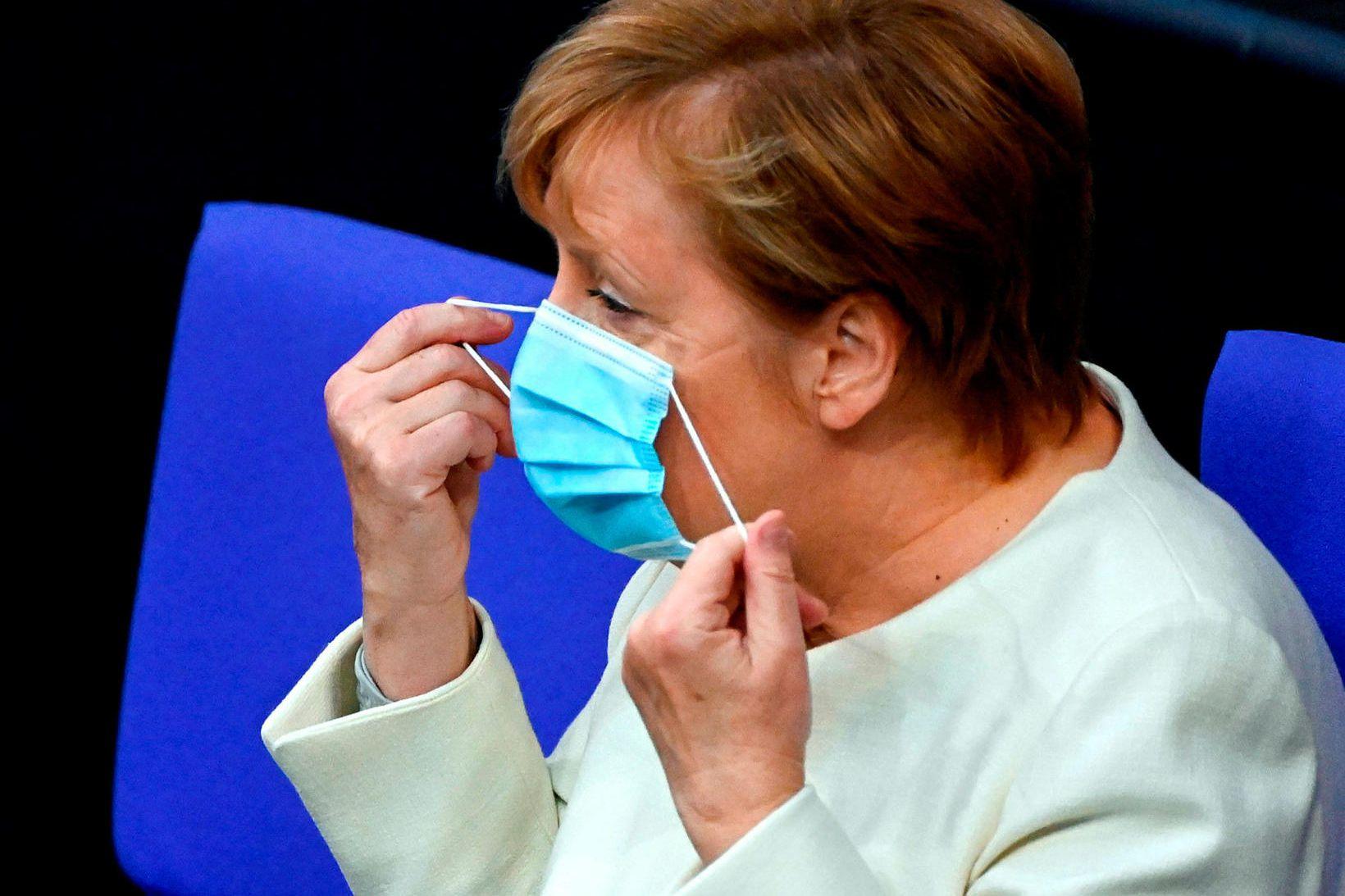 Kanslari Þýskalands, Angela Merkel, sést hér taka af sér grímuna …