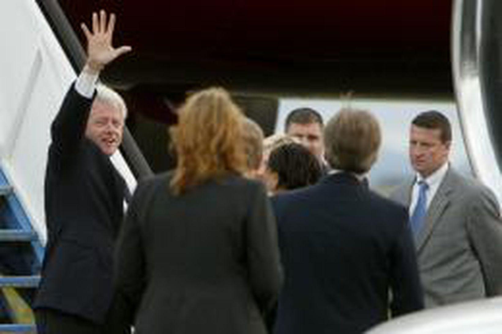 Bill Clinton veifar til viðstaddra áður en hann gengur um …