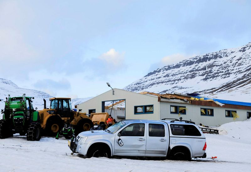 The damaged machinery shed and the pickup truck.
