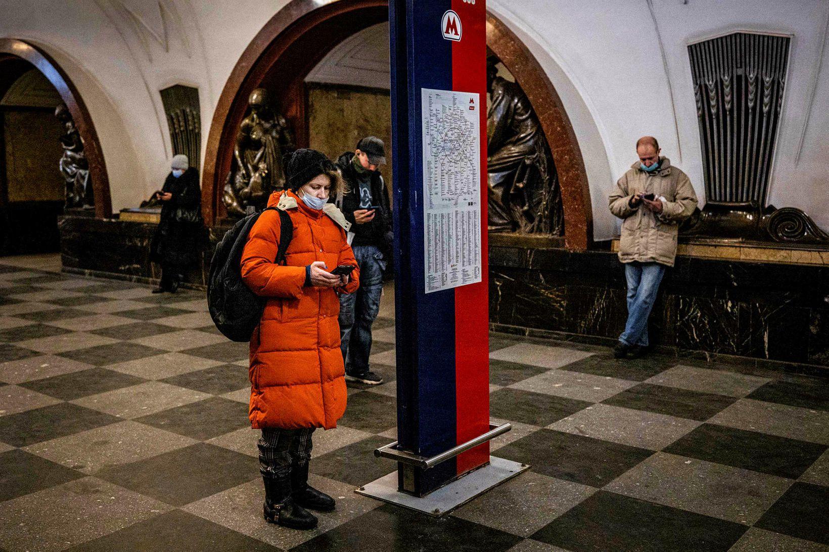 Fólk skoðar farsíma sína á neðanjarðarlestarstöð í Moskvu í dag.