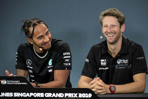 Eitthvað finnst Lewis Hamilton (t.v.) fyndið við það sem Romain Grosjean sagði á blaðamannafundinum í …