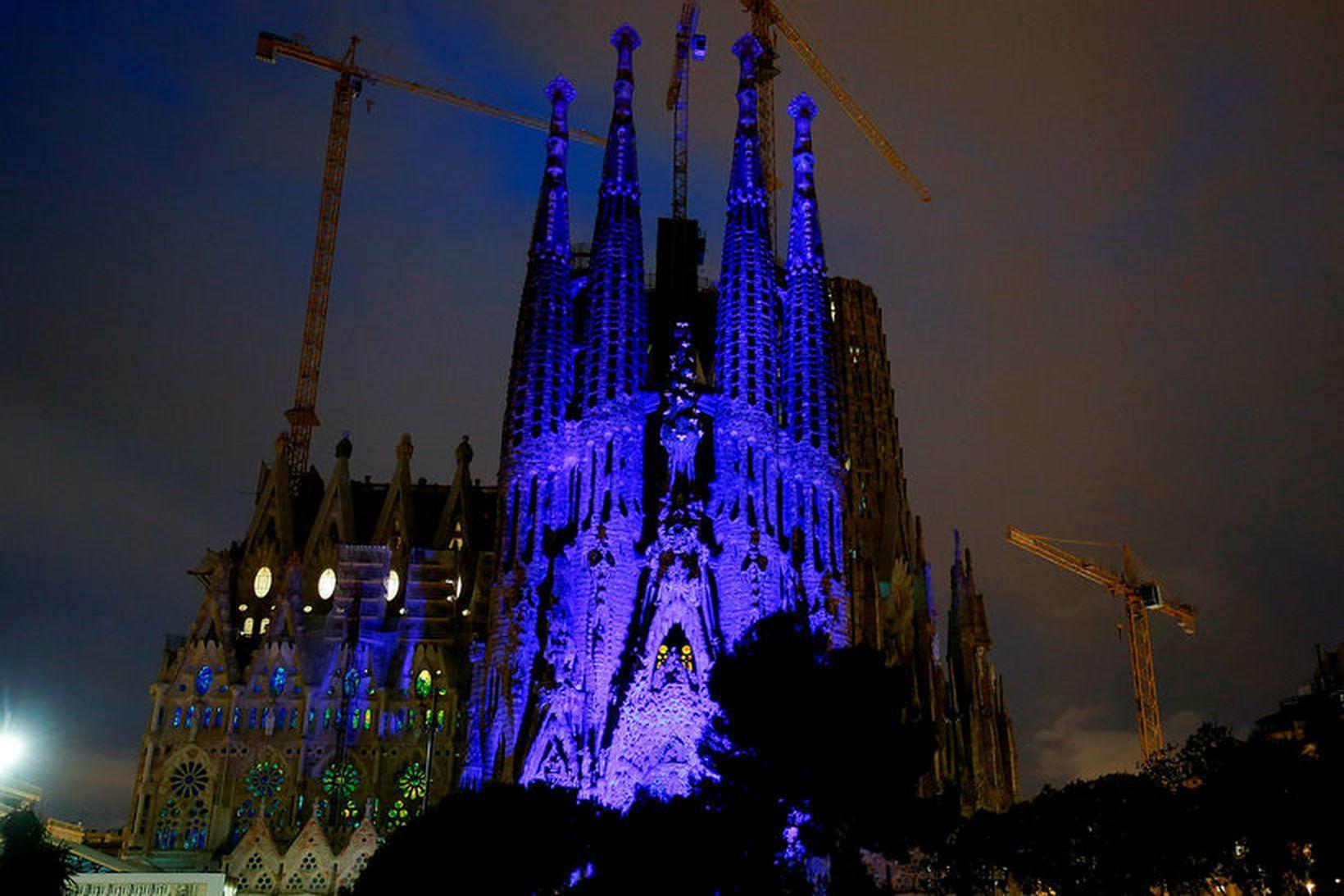 Sagrada Familia kirkjan í Barcelona lýst upp í bláum lit …