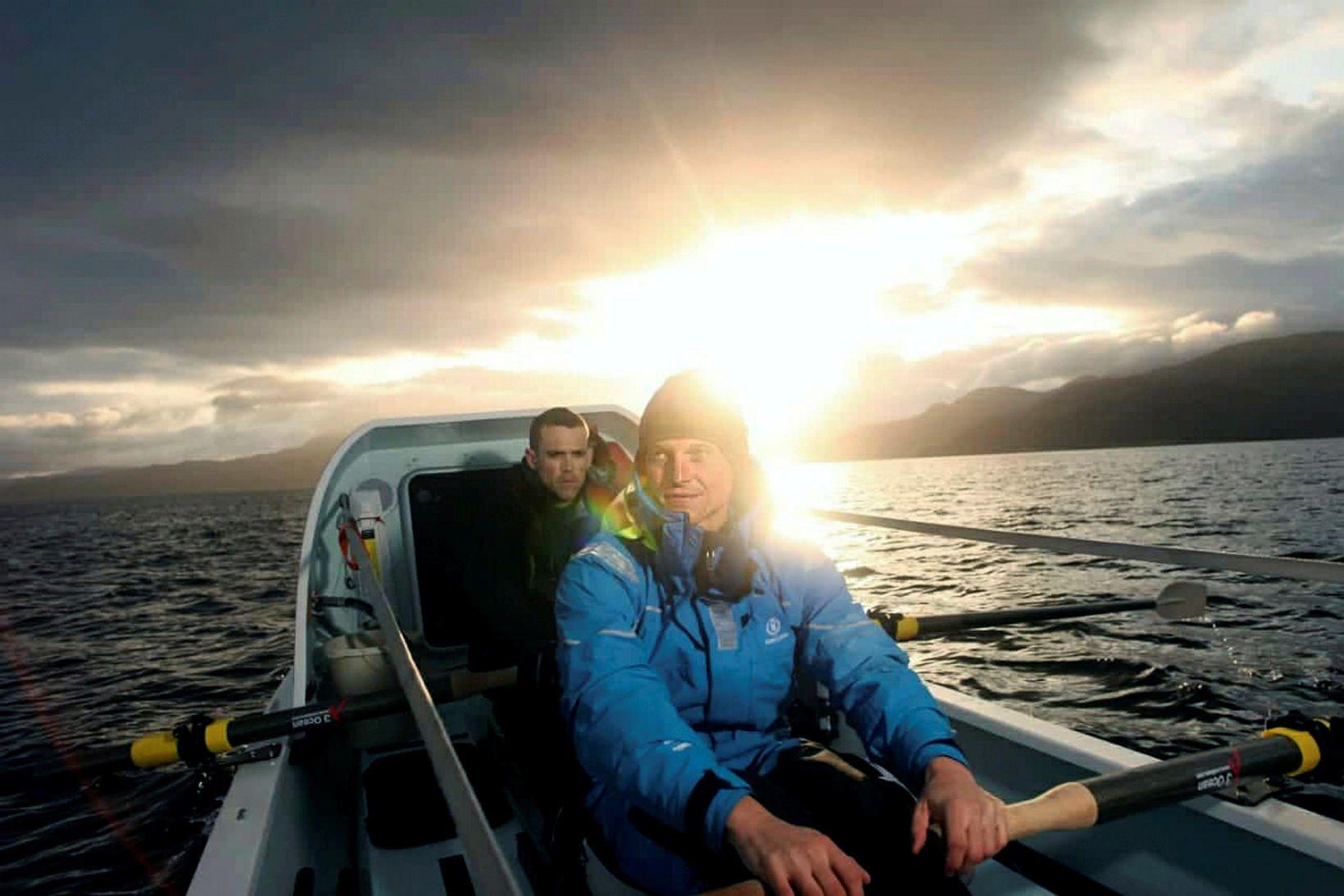 Fiann reri á Suðurskautslandið. Á bak við hann situr Andrew …