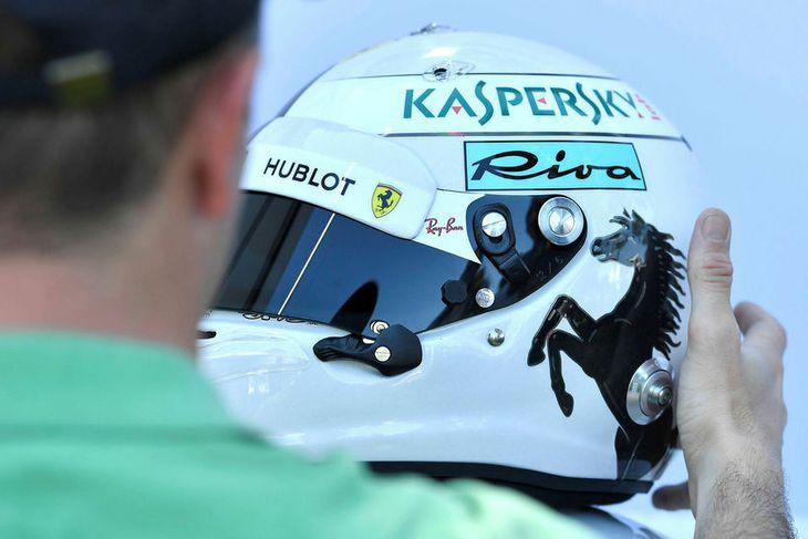 Ljósmyndari hagræðir hjálmi Sebastians Vettel við myndatöku í Melbourne.