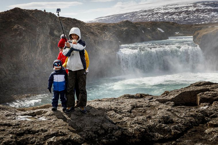 Tourists by Goðafoss waterfall, North Iceland.