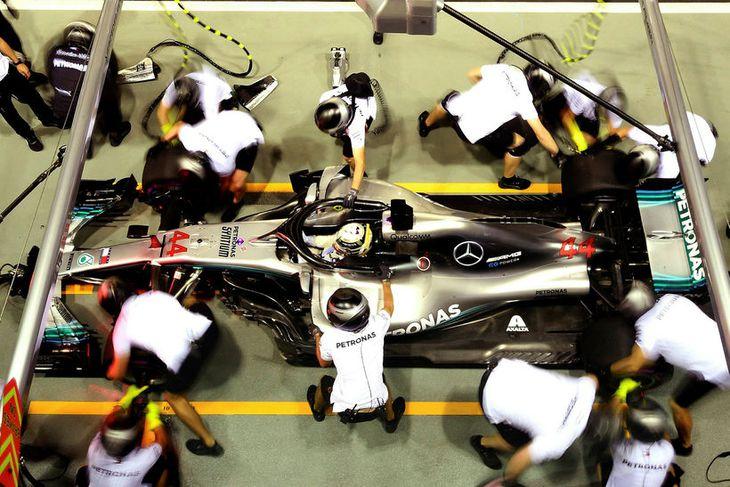 Lewis Hamilton þjónustaður milli aksturslota á seinni æfingu dagsins í Singapúr.
