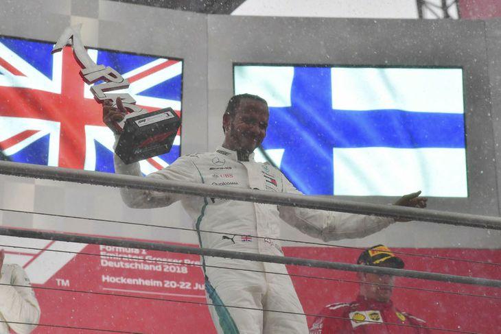 Lewis Hamilton fagnar með sigurgripinn á verðlaunapallinum íæ Hockenheim.