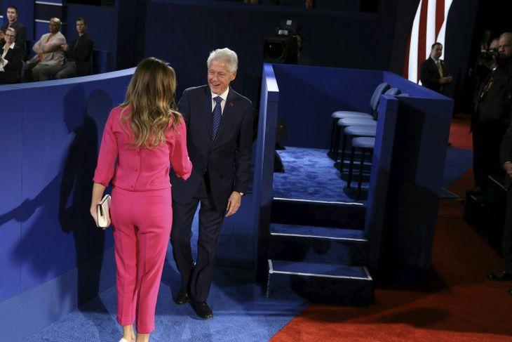 Eiginmaður Hillary Clinton, Bill, heilsar eiginkonu Donalds Trump, Melania.