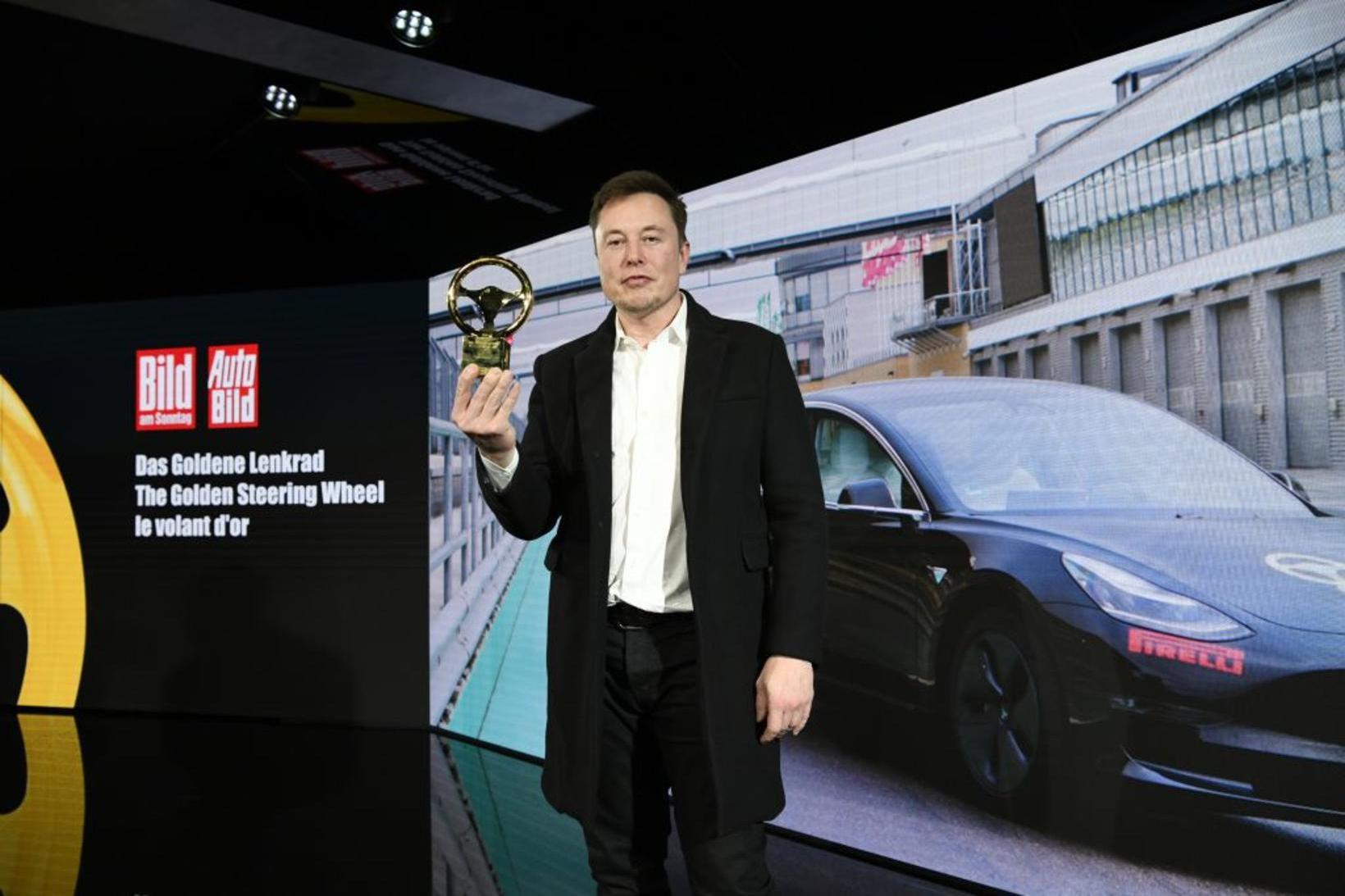 Elion Musk með gullstýrið þýska sem Model 3 færði honum.