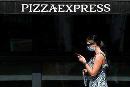 Kona með grímu gengur fram hjá veitingastað Pizza Express í London.